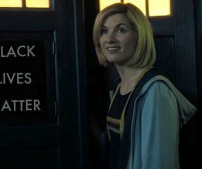 """The 13th Doctor standing in front of the TARDIS, whose sign reads """"Black Lives Matter"""""""